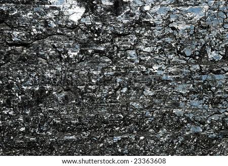 Black reflective surface of bituminous coal, mineral wealth under daylight - stock photo