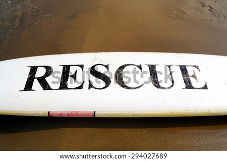 Black Rescue Sign on White Surfboard  - stock photo