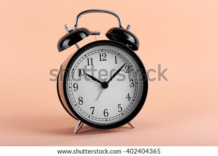 Black retro alarm clock on peach background