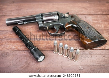 Black revolver gun and and tactical flashlight lying over on wooden background. - stock photo