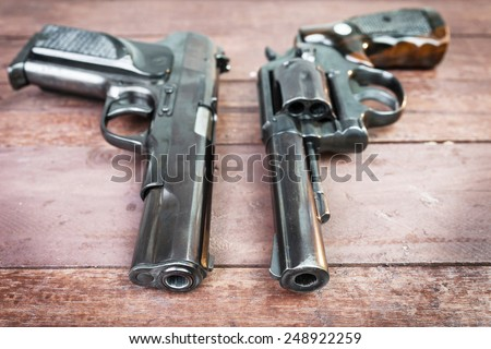 Black revolver gun and Semi-automatic 9mm gun on wooden background. - stock photo