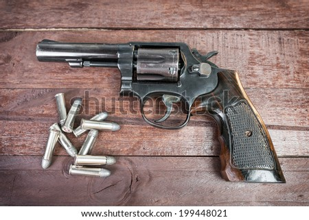 black revolver gun with bullets isolated on wooden background  - stock photo