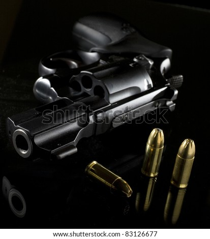 black revolver that is on a glass table with ammo nearby - stock photo