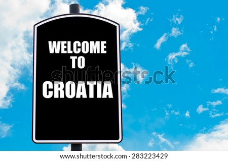 Black road sign with greeting message WELCOME TO CROATIA isolated over clear blue sky background with available copy space. Travel destination concept  image