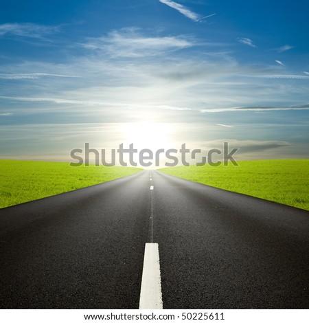 Black roadway against an amazing sunrise - stock photo