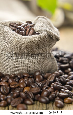 Black roasted coffee beans in a small burlap sack - stock photo