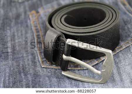 Black rolled belt on jeans - stock photo