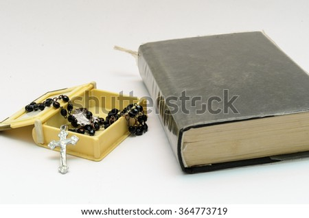 black rosary beads in box, close to small bible on white background - stock photo