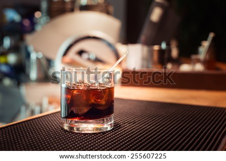 Black russian cocktail on the bar stand on rubber mat. Shallow DOF and marsala tonned - stock photo