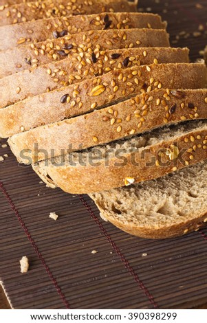 Black rye bread with sliced layer of seeds and nuts - stock photo