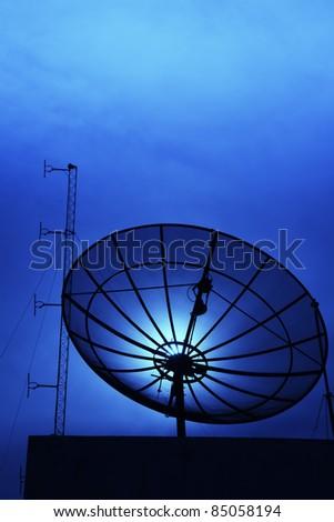 black satellite dish beside FM broadcast antenna - stock photo
