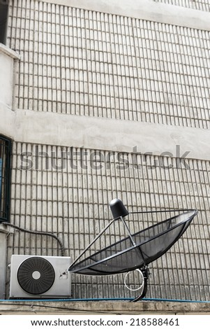 black satellite dish install at side of building - stock photo