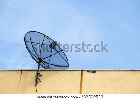 black satellite disk on deck of building in sunny day - stock photo