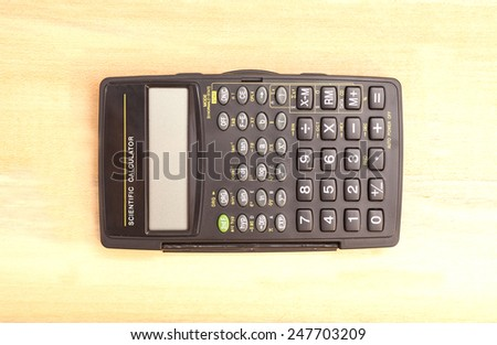 Black  scientific calculator  on wooden background