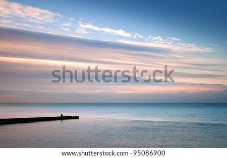 Black Sea coast, lonely fisherman on the small stone pier. Sochi, Adler, Russia - stock photo