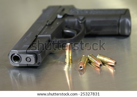 Black semi-automatic handgun with bullets, shallow depth of field - stock photo