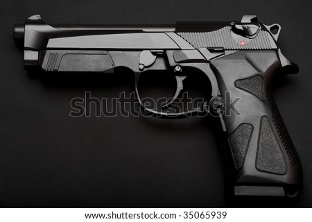 Black semi-automatic pistol on a black background - stock photo