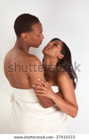 Black sensual couple, African American man and woman of Creole ethnicity hugging wrapped in bathtowel