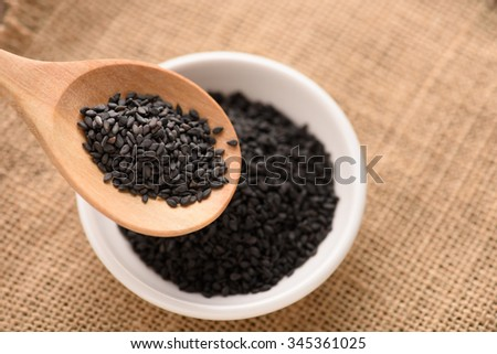 black Sesame close up shot in wood spoon  on sack background - stock photo