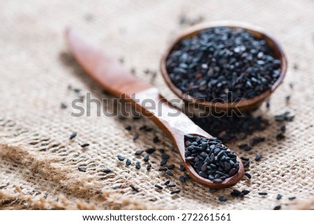 Black Sesame (close-up shot) on rustic wooden background - stock photo