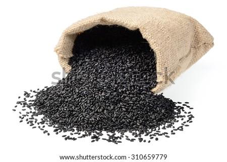black sesame in the sack on white, (large depth of field, taken with tilt shift lens) - stock photo