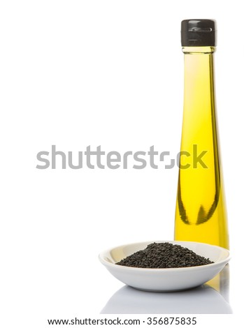 Black sesame seed and a bottle of sesame seed oil over white background - stock photo