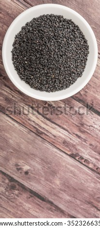 Black sesame seed in white bowl over wicker background