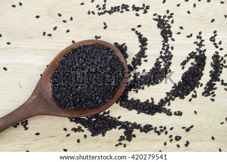 black sesame seed on wooden spoon - stock photo