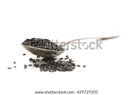 Black sesame seeds. Healthy sesame seeds in spoon  isolated on white background. - stock photo