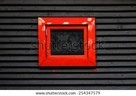 black sheathed wooden wall with red framed window - stock photo