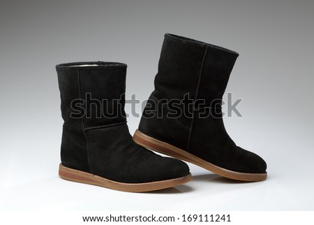 Black sheepskin boots on white background - stock photo