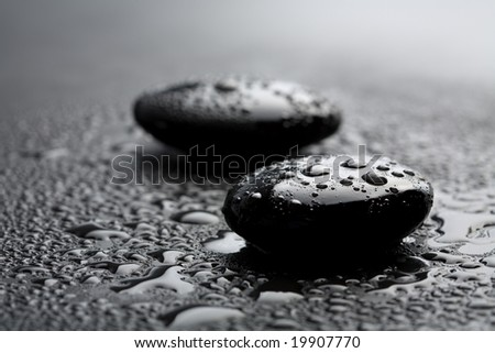 black shiny zen stones with water drops over black background - stock photo
