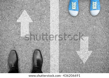 Black shoes and blue shoes standing on different side of the road. Representing family problem like father and son, father and daughter, dad and kid or child. - stock photo