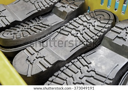 black shoes soles in yellow basket - stock photo