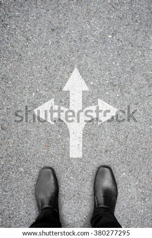 Black shoes standing at the crossroad and has to make a decision which way to go - three ways to choose