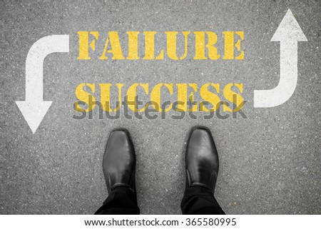 black shoes standing on the asphalt concrete floor with two direction to go - success or failure
