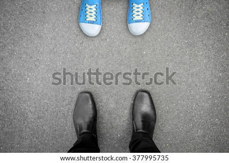 black shoes standing opposite blue shoes like father, mother or parents and their kids are in problem - stock photo