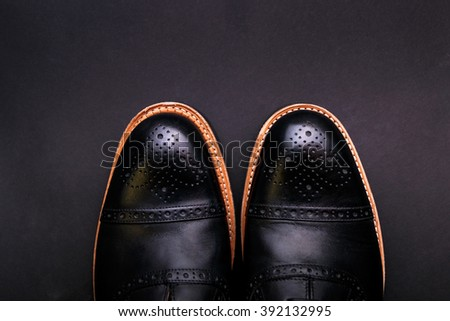Black shoes with a brown sole on a black background  - stock photo