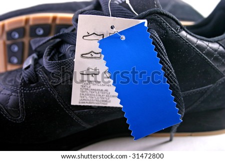 Black shoes with blue tag close up or macro. - stock photo