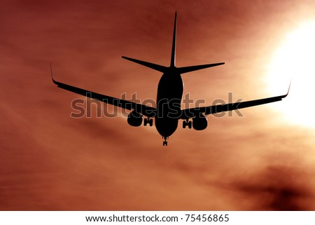black silhouette of airplane against the sun - stock photo