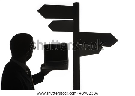 Black silhouette of businessman with laptop computer looking at multiple directional sign, isolated on white background. - stock photo