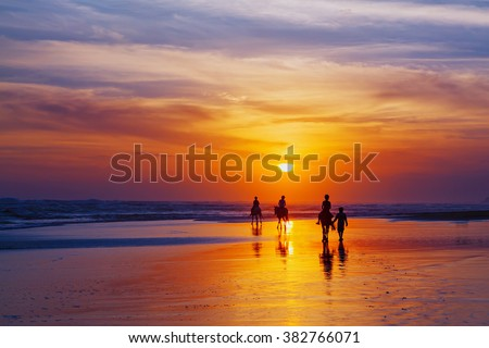 Black silhouette of happy family having horse riding adventure on sand sea beach on background of sunset sky. Active parents and people outdoor activity on tropical summer vacations with children. - stock photo