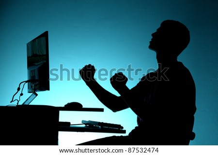 Black silhouette of happy teenager sitting at the computer on blue background - stock photo