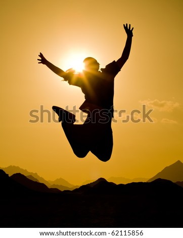 black silhouette of man in happy jump on orange sunset sky and desert mountain background - stock photo