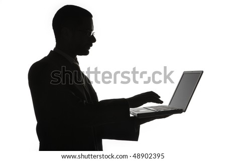 Black silhouette of man typing on laptop computer, isolated on white background. - stock photo