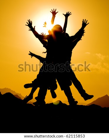black silhouette of people group in happy jump on orange sunset sky and desert mountain background - stock photo