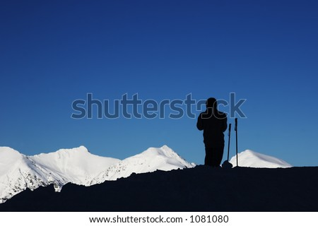 black silhouette of skier, blue sky and white mountain - stock photo