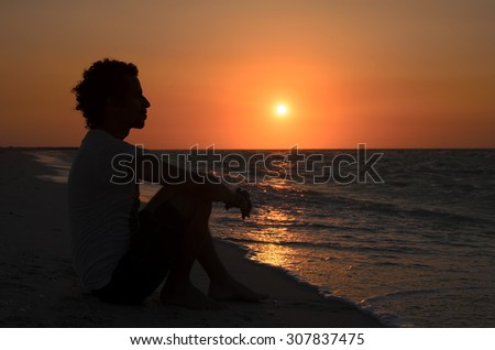 Black silhouette of young man sitting at the beach at sunset