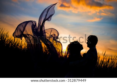 Black silhouettes of men and women against the background of a beautiful sunset, love, dating, kiss, the dress  looks like butterfly wings - stock photo