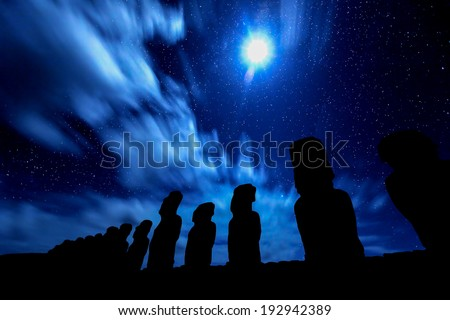 Black silhouettes of standing moais against starry blue sky in Easter Island - stock photo